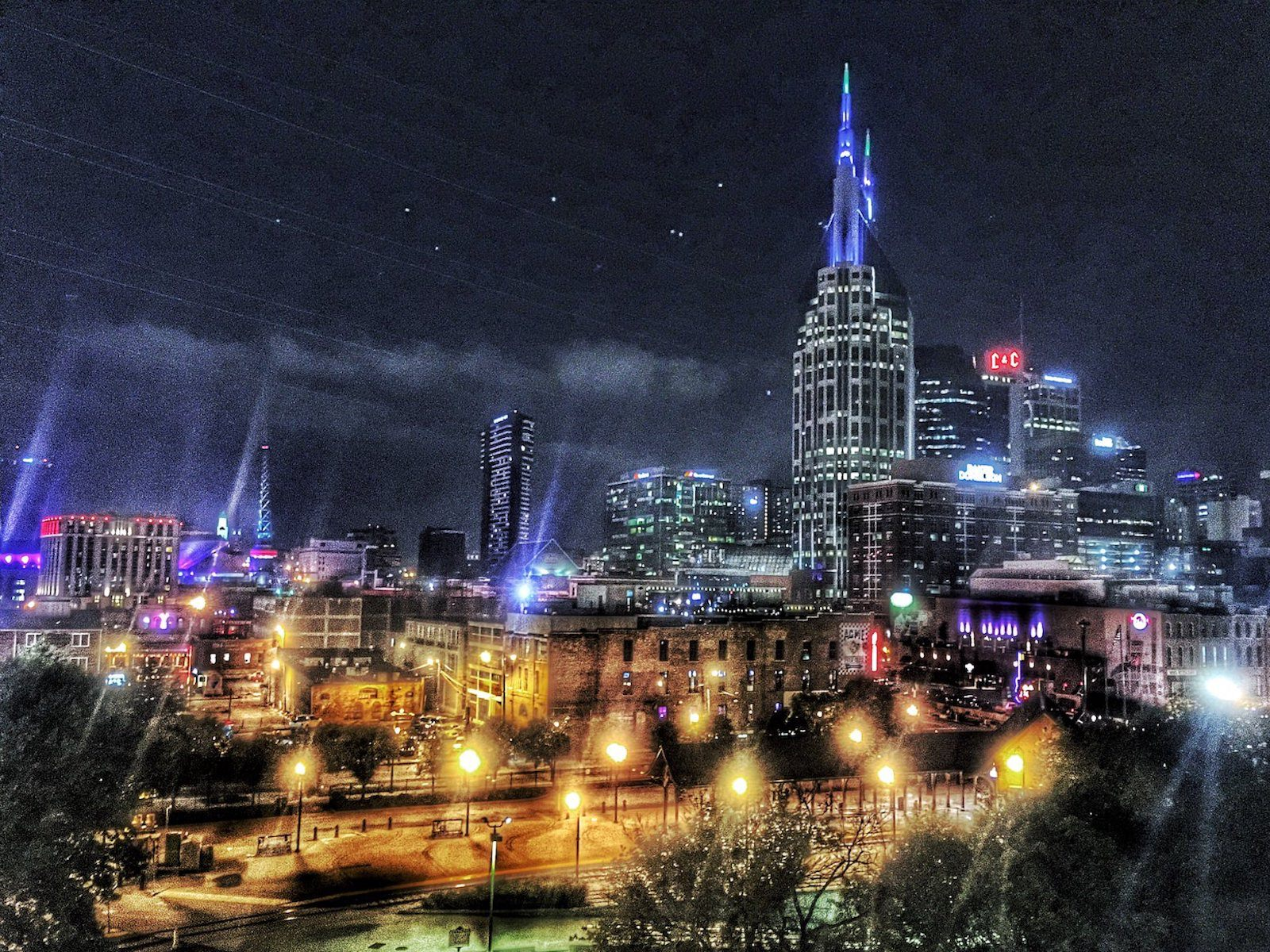 Edited image of Nashville skyline at night with river park in front.