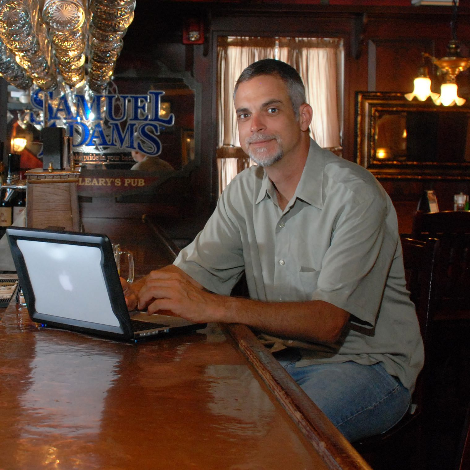 Image of Mark McGuire looking up from MacBook at the bar.