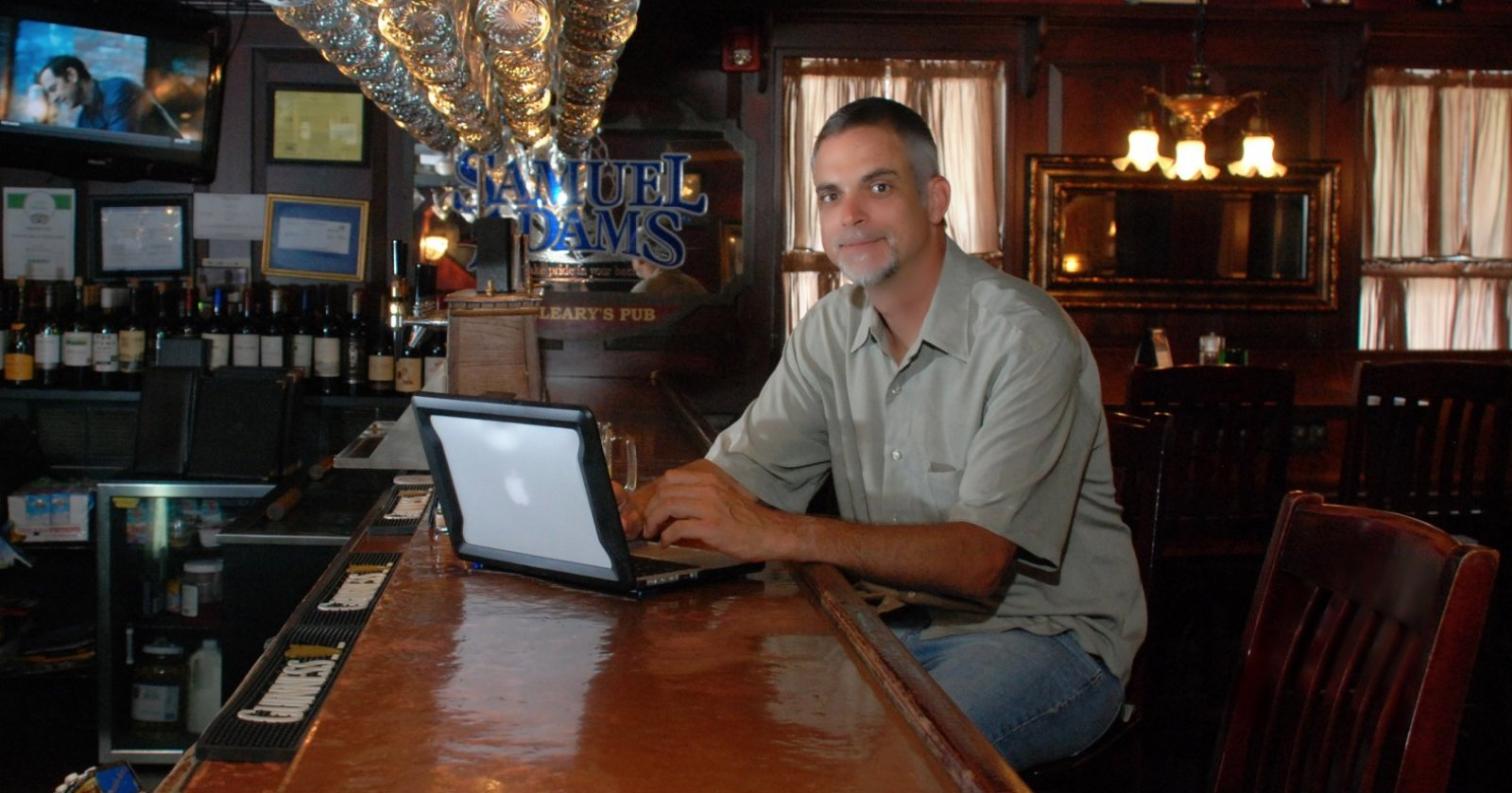 Image of Mark McGuire working on his laptop at the bar.