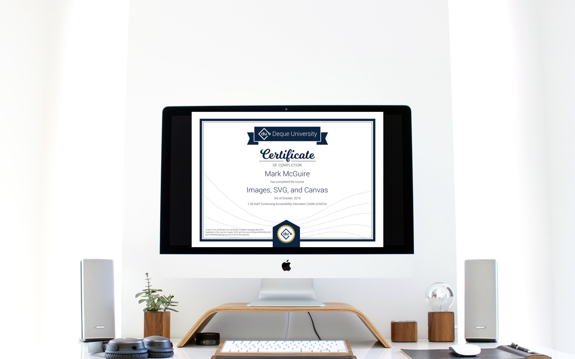 iMac with certificate displayed on screen.