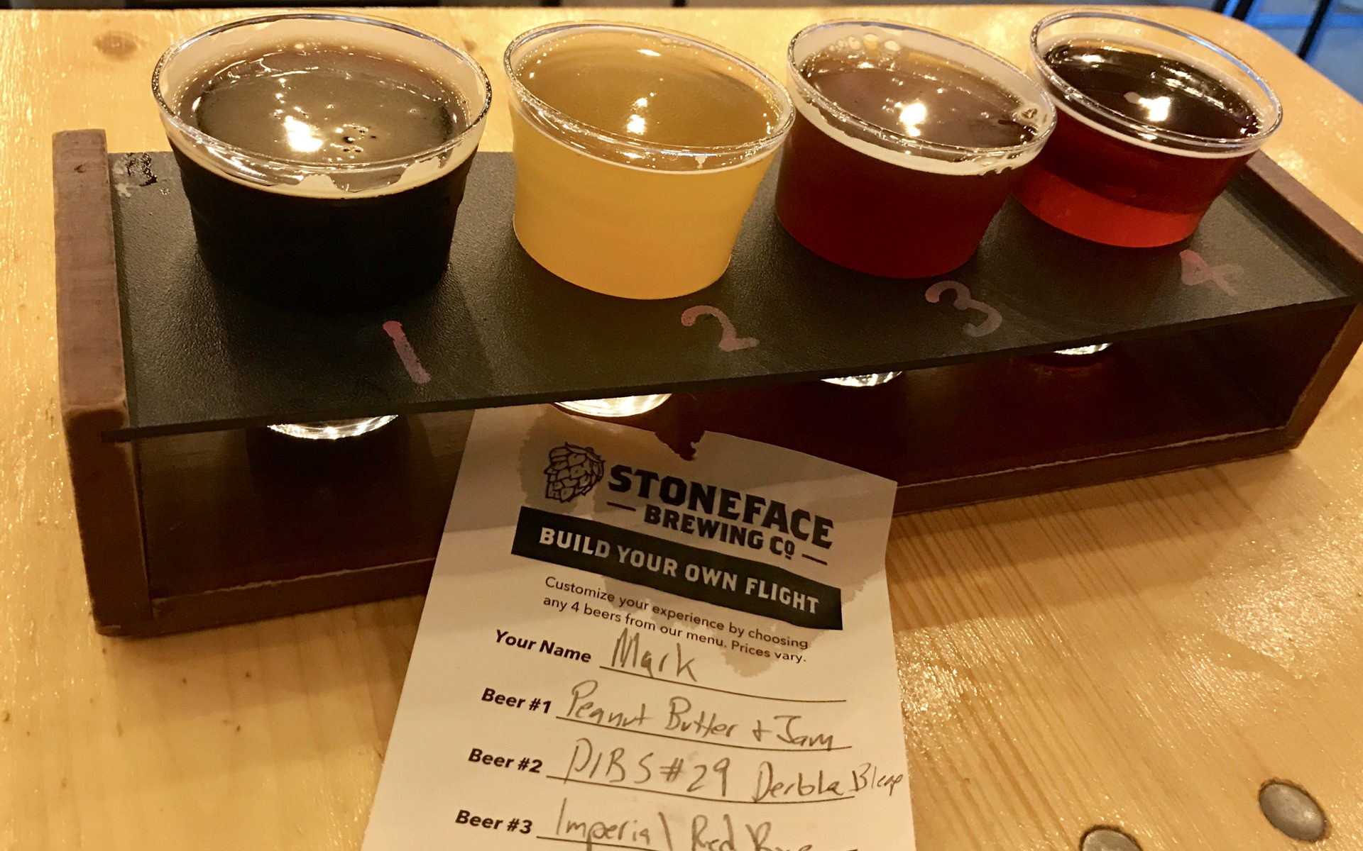 A flight of four beers with a handwritten ticket listing which beer is which.